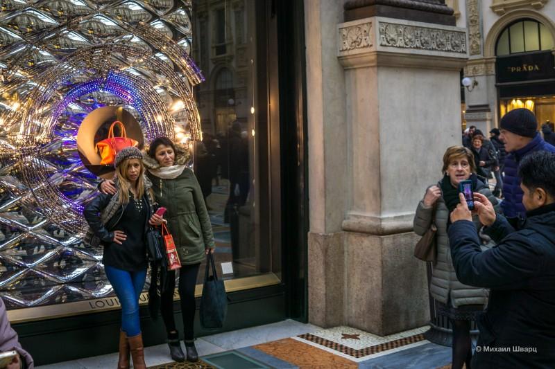Женщины фотографируются с сумкой в витрине